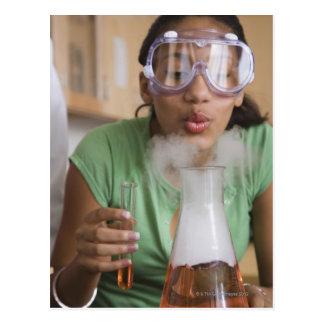 Teenage girl performing science experiment postcard