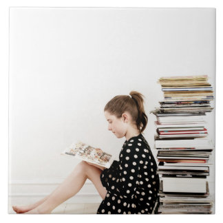 Teenage girl reading comic strip by pile of ceramic tiles