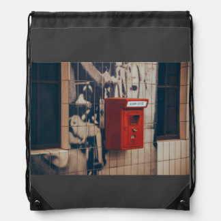 Telephone box on a wall drawstring backpacks