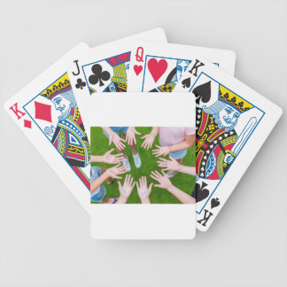 Ten arms of children in circle with palms of hands bicycle playing cards