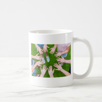 Ten arms of children in circle with palms of hands coffee mug