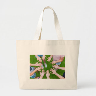 Ten arms of children in circle with palms of hands large tote bag