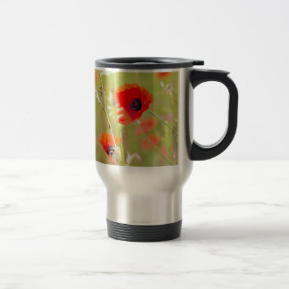 Tender shot of red poppies on the field travel mug