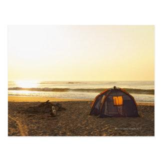 Tente et feu de camp de burn-out sur la plage cartes postales