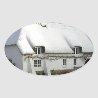 Thatched English Cottage in Snow Oval Sticker