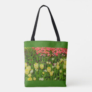 the blossoming of tulips in a park  tote bag