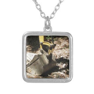The bucket of the excavator sits at rest silver plated necklace