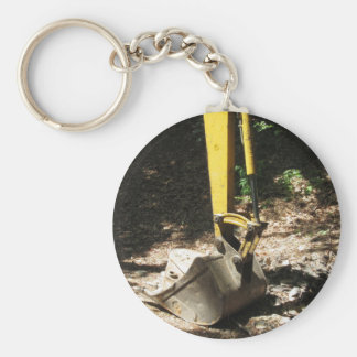 The bucket of the yellow excavator sits at rest basic round button keychain