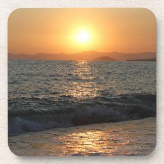 The sun sets over a beautiful mountain range, drink coaster