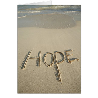 The word 'Hope' sand written on the beach with Card