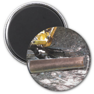 The yellow snowplow sits at rest in the wood 2 inch round magnet