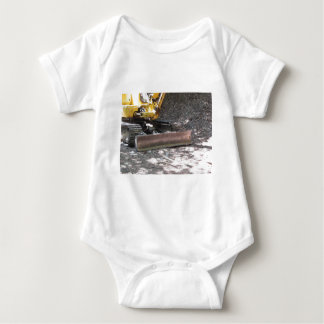 The yellow snowplow sits at rest in the wood baby bodysuit