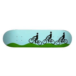 Three cyclists skate board