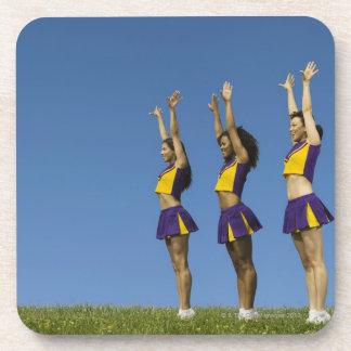 Three female cheerleaders standing in row drink coasters