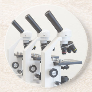 Three microscopes in a row isolated on background beverage coaster