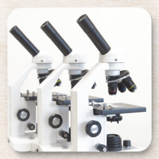 Three microscopes in a row isolated on background coaster