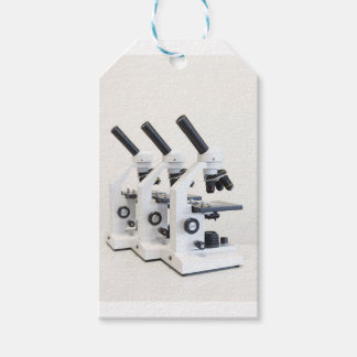 Three microscopes in a row isolated on background gift tags
