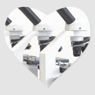 Three microscopes in a row isolated on background heart sticker