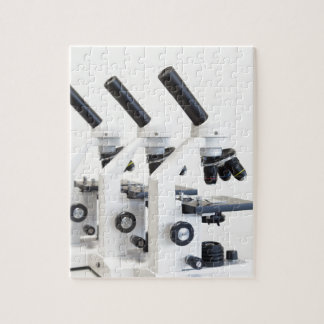 Three microscopes in a row isolated on background jigsaw puzzle