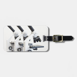 Three microscopes in a row isolated on background luggage tag