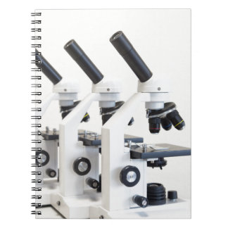 Three microscopes in a row isolated on background notebooks