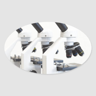 Three microscopes in a row isolated on background oval sticker