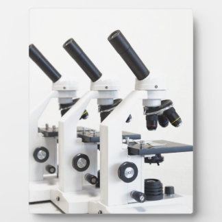 Three microscopes in a row isolated on background plaque
