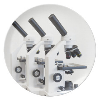 Three microscopes in a row isolated on background plate