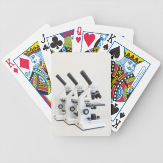 Three microscopes in a row isolated on background poker deck