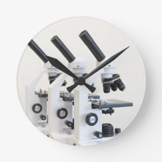 Three microscopes in a row isolated on background round clock