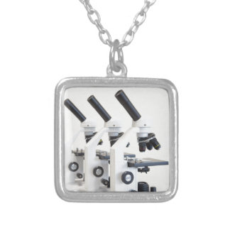 Three microscopes in a row isolated on background silver plated necklace