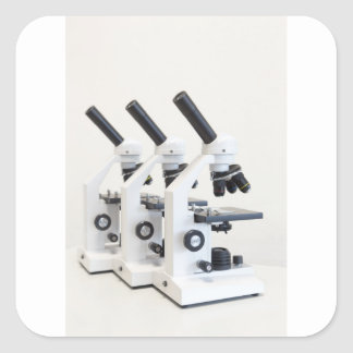 Three microscopes in a row isolated on background square sticker