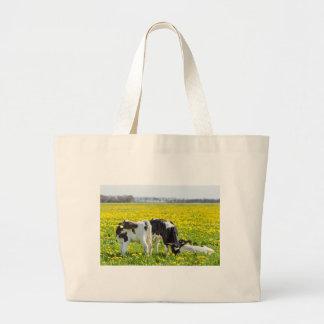 Three newborn calfs in spring dandelions meadow large tote bag