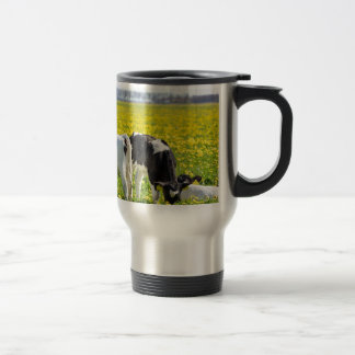 Three newborn calfs in spring dandelions meadow travel mug