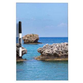 Three separate rocks offshore in sea dry erase board