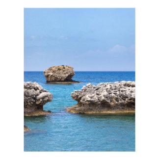 Three separate rocks offshore in sea letterhead