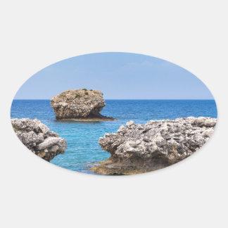 Three separate rocks offshore in sea oval sticker