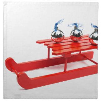 Three silver christmas balls on red sledge napkin