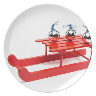 Three silver christmas balls on red sledge plate