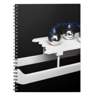 Three silver christmas balls on white sleigh notebook