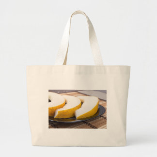 Three slices of juicy yellow melon large tote bag