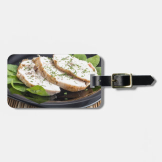 Three slices of roasted chicken on a black plate luggage tag