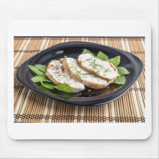 Three slices of roasted chicken on a black plate mouse pad