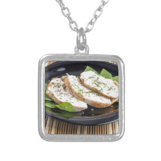 Three slices of roasted chicken on a black plate silver plated necklace