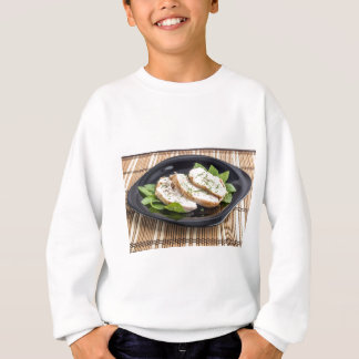 Three slices of roasted chicken on a black plate sweatshirt