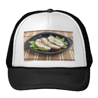 Three slices of roasted chicken on a black plate trucker hat