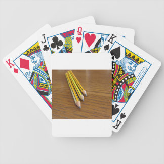 Three used pencils on wooden table bicycle playing cards