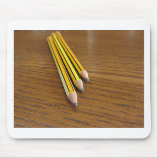 Three used pencils on wooden table mouse pad