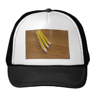 Three used pencils on wooden table trucker hat