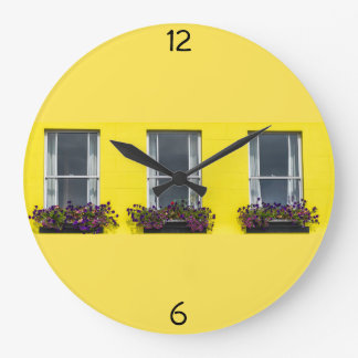 Three windows on a yellow wall clock